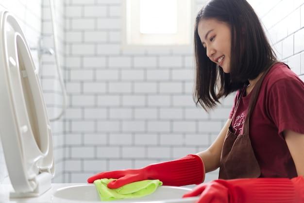 A menina asiática com as luvas de borracha vermelhas está limpando a bacia de toalete. Foto Premium