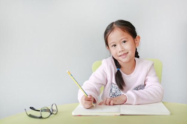 A menina asiática pequena de sorriso da criança escreve em um livro ou em um caderno com o lápis na tabela na sala de aula. Foto Premium
