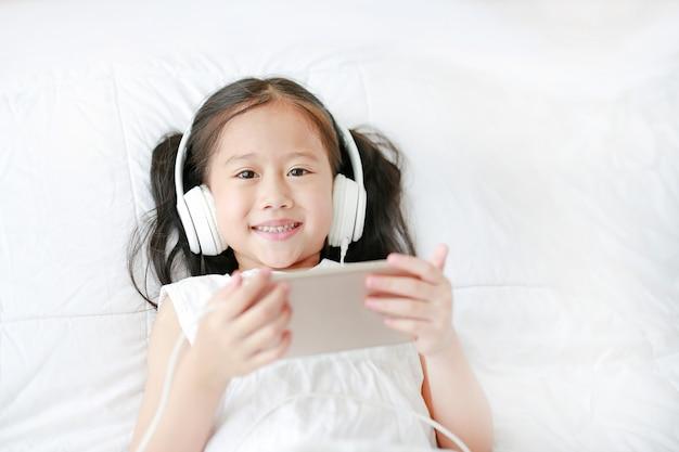 A menina asiática pequena feliz que usa fones de ouvido escuta música pelo smartphone que sorri e que olha a câmera ao encontrar-se na cama em casa. Foto Premium