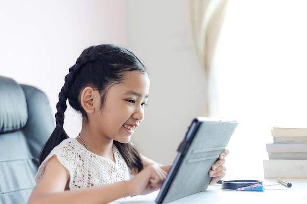 A menina asiática pequena que usa a tabuleta e sorri com felicidade para o conceito da educação seleciona a profundidade de foco rasa do campo Foto Premium