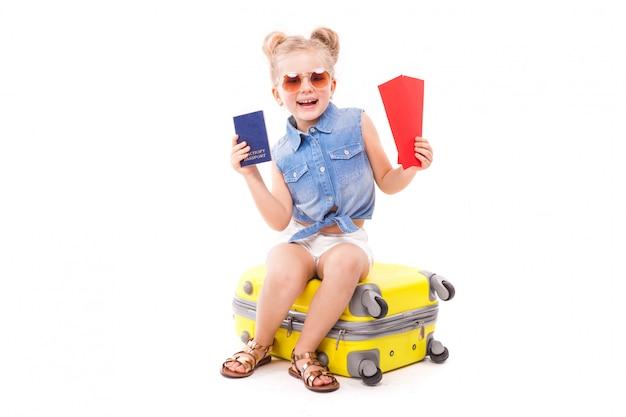 A menina atrativa na camisa azul, no short branco e nos óculos de sol senta-se na mala de viagem amarela Foto Premium