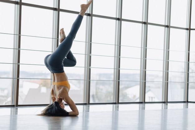 A menina atrativa nova que faz a aptidão exercita com ioga no assoalho. janelas panorâmicas Foto Premium