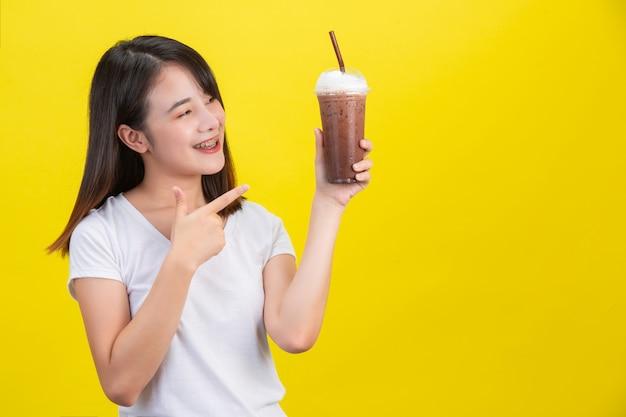 A menina bebe água fria de cacau de um copo de plástico transparente em um amarelo. Foto gratuita