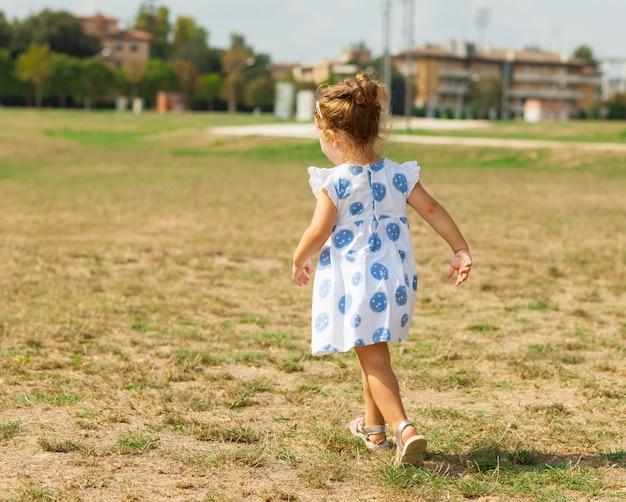 A menina bonita joga ao ar livre em um dia de verão. Foto Premium
