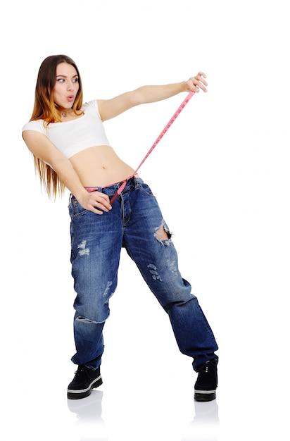 A menina bonita mede a cintura e aprecia uma figura magro em um fundo branco. perda de peso, perda de peso, dieta. Foto Premium