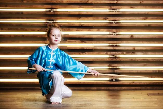A menina bonita na sala em roupas esportivas para artes marciais é wushu ou kung fu Foto Premium