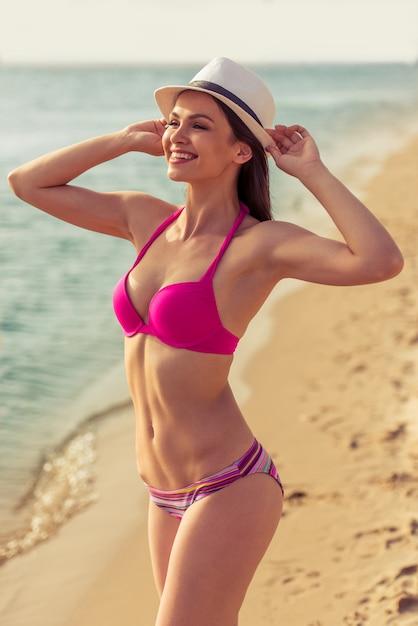 A menina bonita no roupa de banho cor-de-rosa está pondo o chapéu sobre a cabeça. Foto Premium
