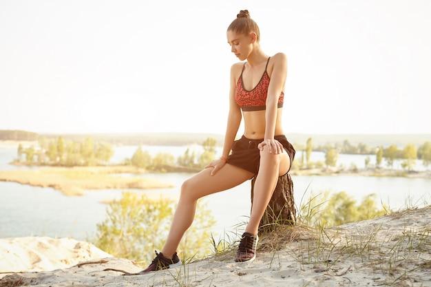 A menina bonita nova vestiu-se no sportswear e nas sapatilhas senta-se em um coto Foto Premium