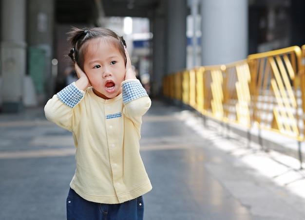 A menina bonito da criança pequena que interrompe suas orelhas, guardando suas mãos cobre as orelhas para não ouvir-se Foto Premium