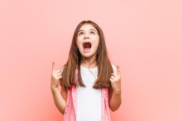 A menina bonito indica com ambos os dedos dianteiros acima de mostrar um espaço vazio. Foto Premium