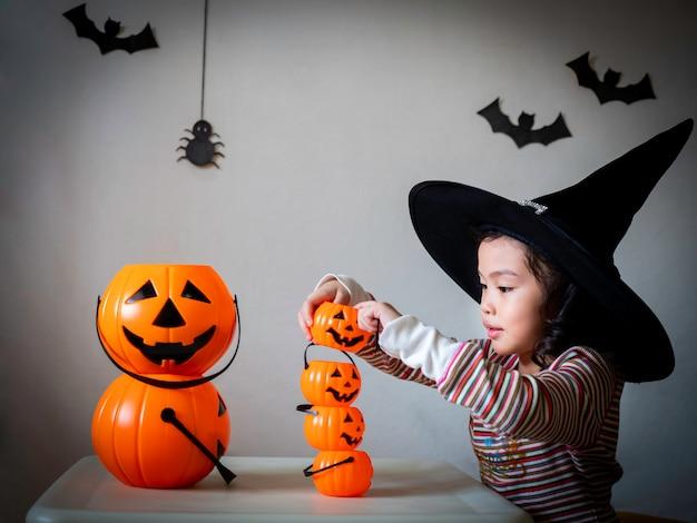 A menina bonito pequena cosplay como uma bruxa e um jogo empilha as cubetas das abóboras sobre o fundo escuro com aranhas e bastões. Foto Premium