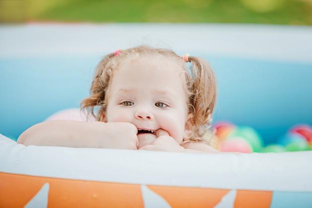 A menina brincando com brinquedos na piscina inflável no dia ensolarado de verão Foto gratuita