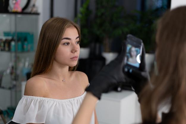 A menina caucasiano nova do esteticista prende a correção da sobrancelha modelo Foto Premium