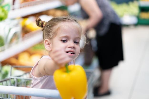 A menina caucasiano pequena escolhe legumes frescos no supermercado. Foto Premium