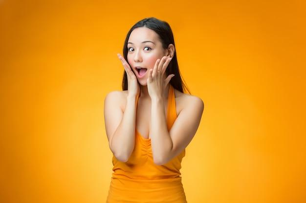 A menina chinesa surpresa na parede amarela Foto gratuita