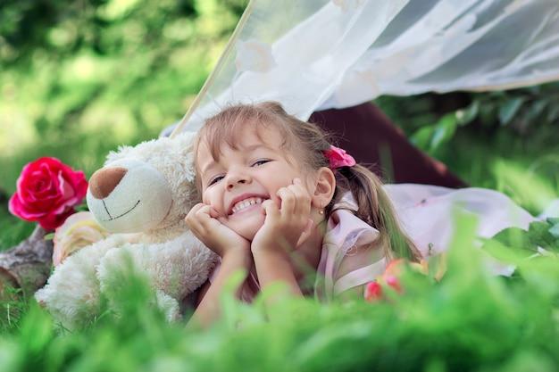 A menina coloca deitado ao ar livre com um ursinho de pelúcia e ri Foto Premium