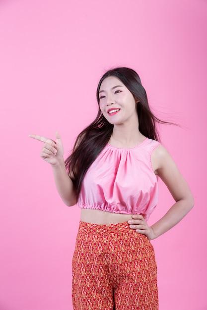 A menina da forma veste-se acima com gestos de mão em um fundo cor-de-rosa. Foto gratuita