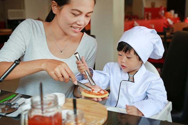 A menina da mãe e da criança em um terno do cozinheiro chefe pequeno faz a mini pizza, cozinhando o conceito da criança. Foto Premium
