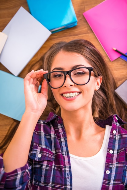 A menina de óculos encontra-se no chão e sorri. Foto Premium