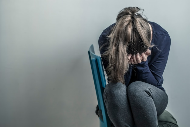 A menina depressiva e desesperada senta-se em uma cadeira. mulher jovem triste. copie o espaço. Foto Premium