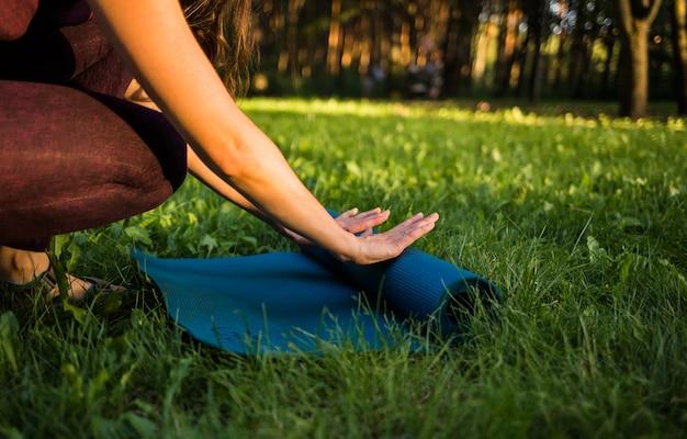 A menina desenrola um tapete de ioga na natureza Foto Premium