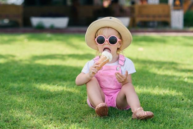 A menina elegante da criança em um chapéu e em óculos de sol cor-de-rosa come com gelado de prazer em um gramado verde em um dia ensolarado e quente. Foto Premium
