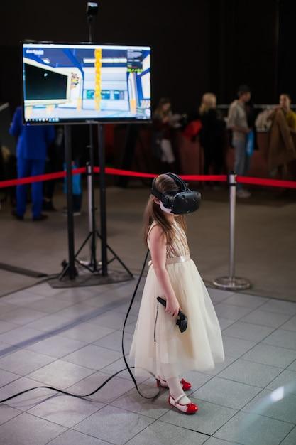 A menina em um vestido bonito e em vidros da realidade virtual em sua cabeça joga o jogo do vr na exposição da tecnologia. Foto Premium