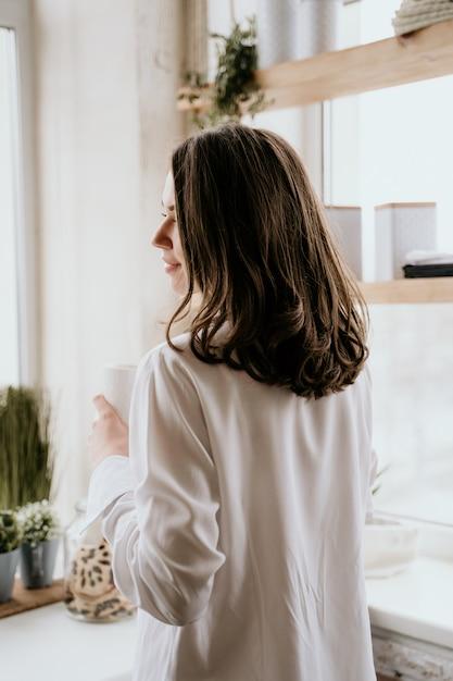 A menina em uma camisa branca bebe o café na manhã em uma cozinha. Foto Premium