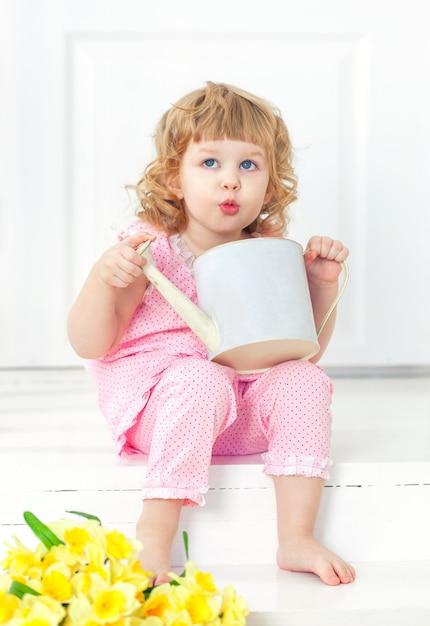 A menina encaracolado pequena no vestido cor-de-rosa e descalça senta-se em um patamar branco e em jogar com lata molhando. Foto Premium