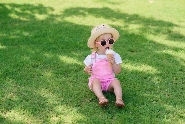 A menina engraçada da criança que veste macacões cor-de-rosa do verão, chapéu e óculos de sol cor-de-rosa senta-se em um gramado verde come o gelado branco de baunilha em um jardim ensolarado. Foto Premium