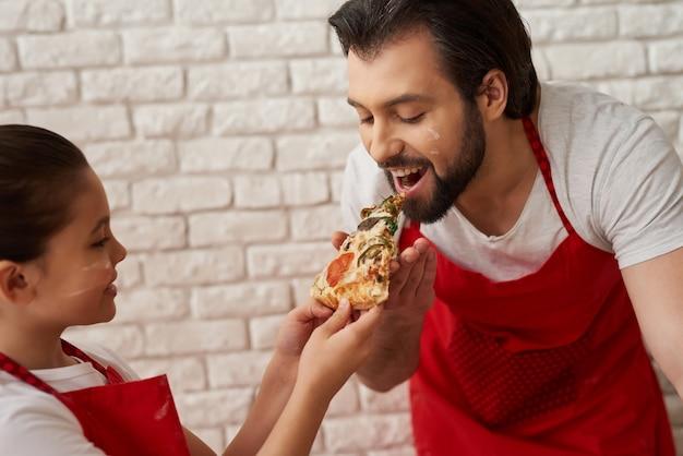 A menina está alimentando o pai com uma fatia de pizza. Foto Premium