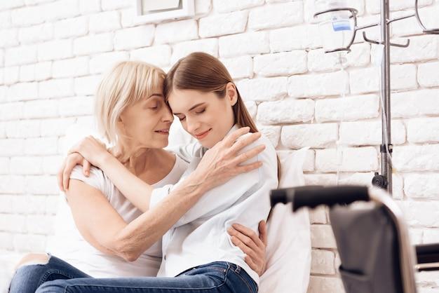 A menina está amamentando a mulher idosa na cama na clínica Foto Premium