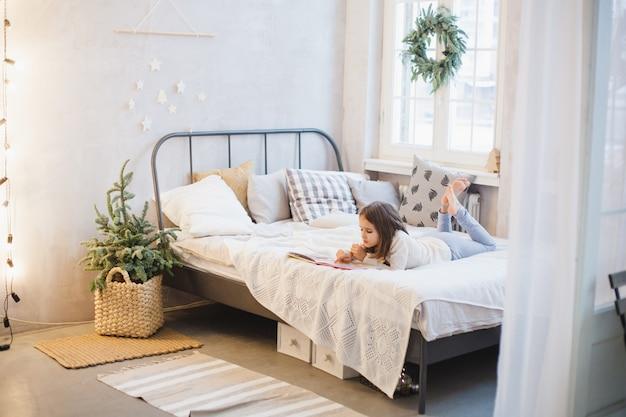 A menina está deitada no sofá e lendo um livro, a sala está decorada para o natal Foto Premium