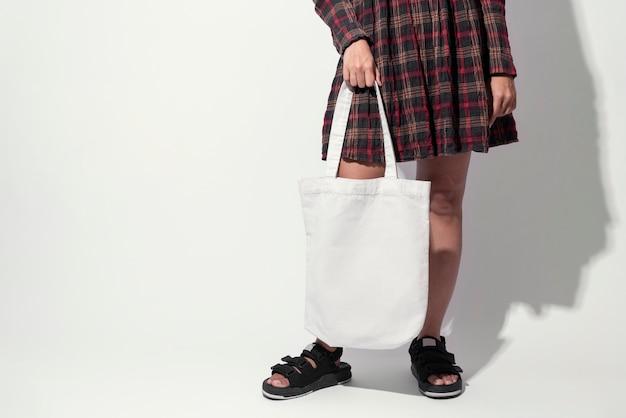 A menina está guardando o tecido da lona do saco. Foto Premium