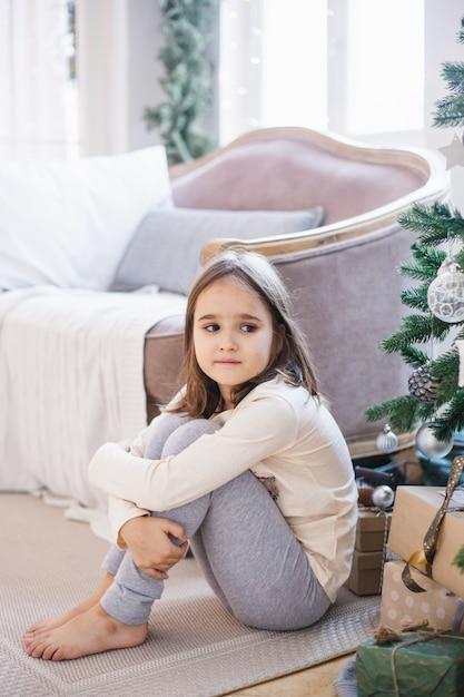 A menina está sentada perto do sofá e decorada com árvore de natal, a sala está decorada para o natal Foto Premium