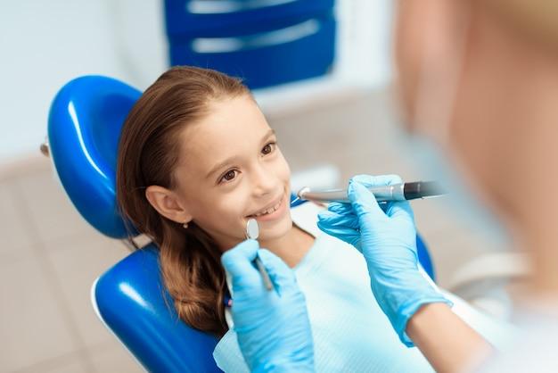 A menina está sentando-se em uma cadeira dental na recepção de um dentista. Foto Premium
