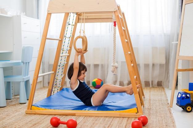 A menina executa exercícios ginásticos em um complexo de esportes em casa de madeira Foto Premium