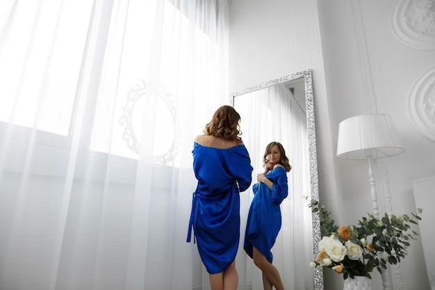 A menina experimenta uma roupa em uma loja de provadores em frente ao espelho Foto Premium
