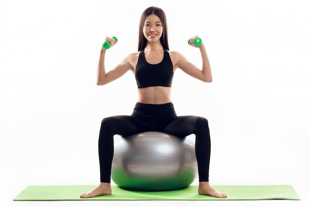 A menina faz exercícios com halteres na bola de ginástica. Foto Premium