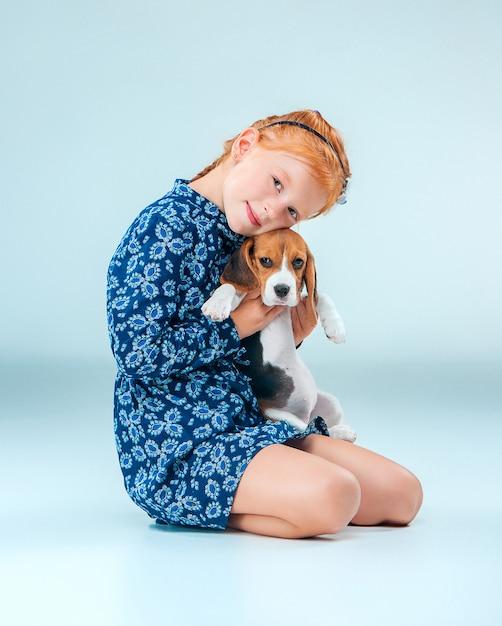A menina feliz e um filhote de cachorro beagle em fundo cinza Foto gratuita