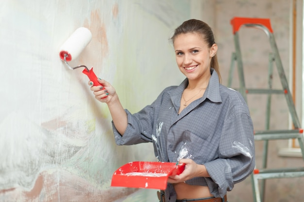 A menina feliz pinta a parede Foto gratuita