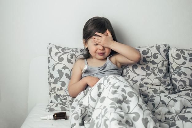 A menina ficou doente. a criança está com febre. termômetro close-up. Foto Premium