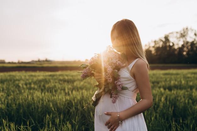 A menina grávida fica no campo Foto gratuita