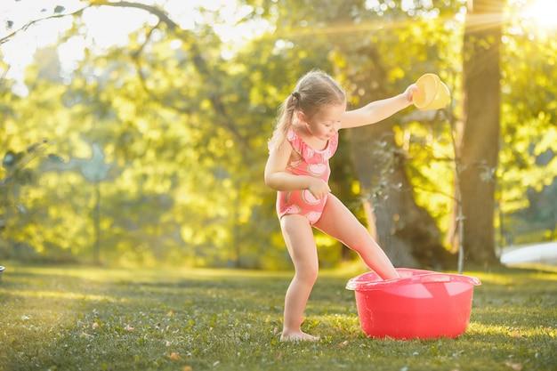 A menina loira bonitinha brincando com salpicos de água no campo no verão Foto gratuita