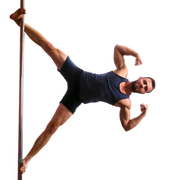 A menina loura atlética nova que faz a força exercita em um pilão. pole dance Foto Premium