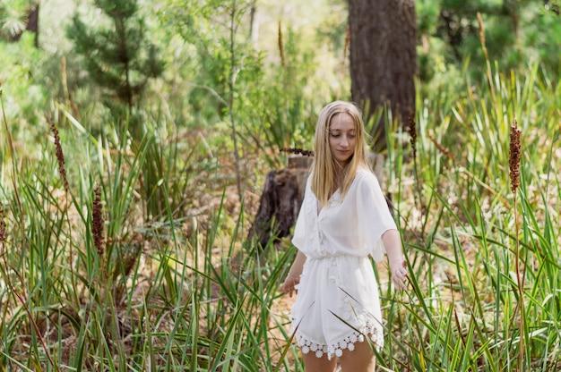 A menina loura bonita que aprecia um dia no parque Foto gratuita