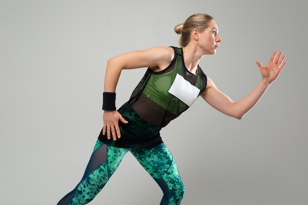 A menina loura forte no sportswear está esticando em um fundo cinzento Foto Premium