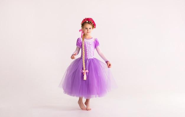 A menina loura pequena que veste a princesa feericamente roxa veste-se no fundo branco. fato de criança para festa de ano novo Foto Premium