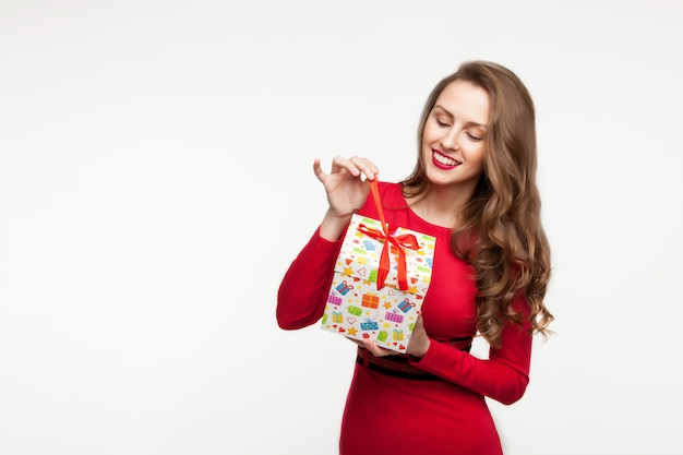 A menina morena está segurando um presente e rindo Foto Premium