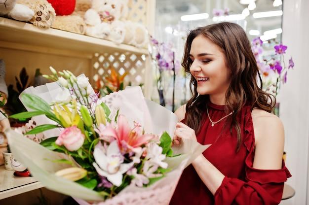 A menina moreno na compra vermelha floresce na loja de flor. Foto Premium